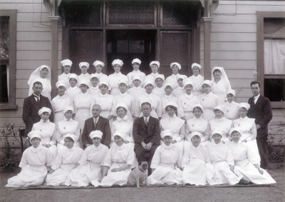 A black and white group photo of nursing staff all wearing white, from the early 1990s